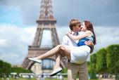 Uomo che porta la sua ragazza tra le sue braccia a parigi — Foto Stock