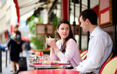 Happy couple drinking coffee or tea in a Parisian outdoor cafe — Foto de Stock