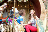 Happy young couple in an equipage of vintage Parisian merry-go-r — Stock Photo