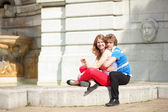 Joyful couple sitting by the fountain — Stock Photo
