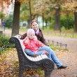 Mother and her adorable daughter sitting on a bench — Foto de Stock