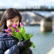 Stock Photo: Happy beautiful girl with tulips enjoying spring day in Paris