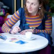 Beautiful girl in bright clothes writing postcards in cafe — Stock Photo #13809102