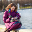 Beautiful girl in bright clothes writing something in her notebo — Stock Photo