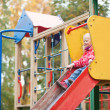 Постер, плакат: Adorable little girl preparing to slither from a slide
