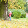 Cute little girl standing close to the tree by fall — Foto de Stock