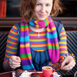 Beautiful girl in colorful clothes in a Parisian street cafe — Stock Photo