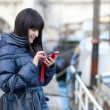 Happy beautiful brunette tourist in Paris sending an sms to a fr — Stock Photo