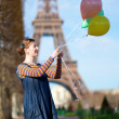 Girl in bright clothes with colourful balloons in Paris near the — Stock Photo #13809245