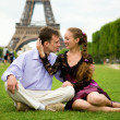 Happy romantic couple in Paris, sitting on grass by the Eiffel T — Stock Photo #13809247