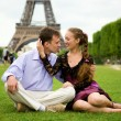 Happy romantic couple in Paris, sitting on grass by the Eiffel T — Stock Photo