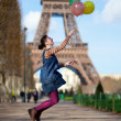 Girl in bright clothes jumping with colourful balloons in Paris — Stock Photo #13809268