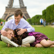 Stock Photo: Happy romantic couple in Paris, sitting on grass by the Eiffel T