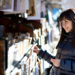 Beautiful woman in Paris selecting a book in an outdoor booksell - Stock Photo