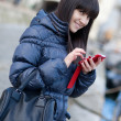 Happy beautiful brunette tourist in Paris sending an sms to some — Foto de Stock