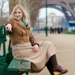 Beautiful blonde woman in Paris, sitting near the Eiffel Tower — Stock Photo