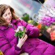 Beautiful girl in bright clothes choosing flowers at market — Stock Photo