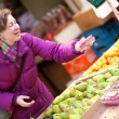 Happy young woman selecting fruits at fruit market — Stock Photo #13809390