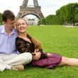 Happy romantic couple in Paris, sitting on grass by the Eiffel T — Stock Photo #13809408