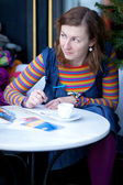 Beautiful girl in bright clothes writing postcards in cafe — Stock Photo