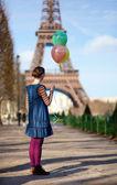 Mädchen in helle kleidung mit bunten luftballons in paris in der nähe der — Stockfoto