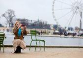 Beautiful woman in Paris using her photo camera — Stock Photo