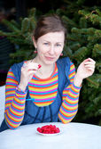 Beautiful girl in bright clothes eating raspberry — Stock Photo