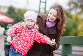 Outdoor portrait of young mother and her beautiful daughter — Stock Photo