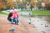 Mother and daughter together on beach by fall, looking at birds — Stockfoto