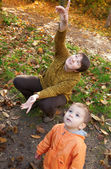 Mother and son in autumn forest, looking at plane in the sky — Stock Photo