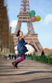 Girl in bright clothes jumping with colourful balloons in Paris — Stock Photo