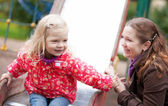 Mother and daughter together on playground — Stock Photo