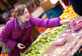 Beautiful girl in bright clothes choosing fruits at fruit market — Stock Photo