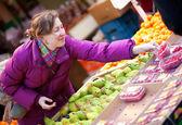 Hermosa chica en ropa brillante elección de frutas en el mercado de la fruta — Foto de Stock