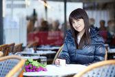 Smiling brunette lady in Parisian street cafe — Stock Photo