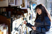 Beautiful woman in Paris selecting a book in an outdoor booksell — Stock Photo