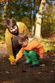 мать и сын, играя с листьями на осень — Стоковое фото