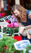красивая молодая женщина, выбирая цветы на рынке — Стоковое фото