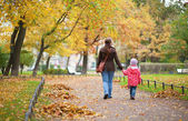 Mother and daughter walking together at beautiful autumn day — Stock Photo