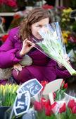 Güzel bir genç kadın çiçek Market seçme — Stok fotoğraf