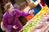 Happy young woman selecting fruits at fruit market — Stock Photo