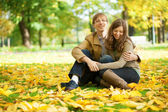 Young couple enjoying bright and warm autumn day in park or fore — Stock Photo