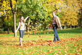 Cheerful couple playing with autumn leaves — Stock Photo