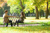 Dating couple on a bench by fall — Stock Photo