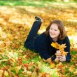 Cheerful girl lying on the ground in park on a fall day — Foto de Stock