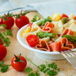 Romantic dinner. Delicious heart-shaped pasta with tomatoes, asp — Stock Photo