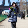 Cheerful young lady walking by the Eiffel tower — Stock Photo