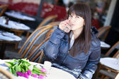Beautiful brunette lady drinking water and coffee in Parisian st — Stock Photo
