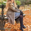 Pretty young lady sitting on the bench and enjoying autumn day — Stock Photo