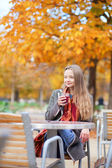 Smiling young lady drinking mulled wine in an outdoor cafe in a — Stock Photo